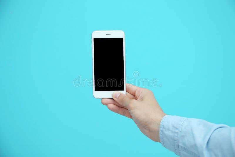 Άτομο που κρατά το κινητό τηλέφωνο με την κενή οθόνη διαθέσιμη στο υπόβαθρο χρώματος στοκ εικόνες