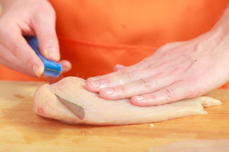 Άτομο που κόβει το ακατέργαστο κρέας κοτόπουλου στον ξύλινο πίνακα στοκ εικόνα με δικαίωμα ελεύθερης χρήσης