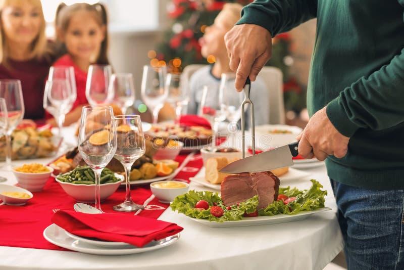 Άτομο που κόβει το νόστιμο ζαμπόν κατά τη διάρκεια του γεύματος Χριστουγέννων στοκ εικόνες