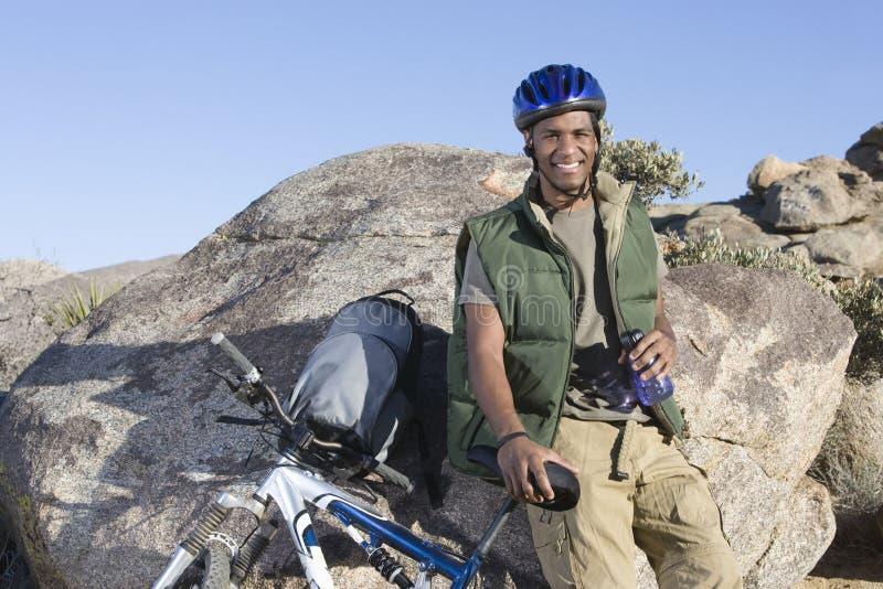 Άτομο που κλίνει ενάντια στο βράχο με το ποδήλατο βουνών στοκ εικόνες