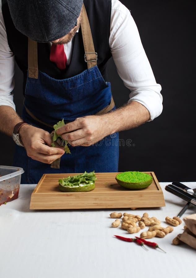 Άτομο που μαγειρεύει πράσινο burger με το βόειο κρέας, τη σαλάτα και τα λαχανικά στοκ εικόνα με δικαίωμα ελεύθερης χρήσης