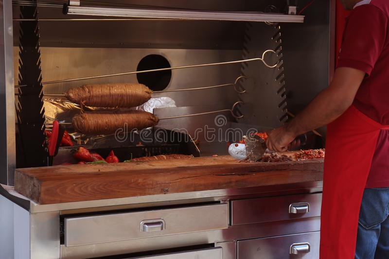 Άτομο που μαγειρεύει το εύγευστο kokoretsi στον πίνακα στοκ εικόνες