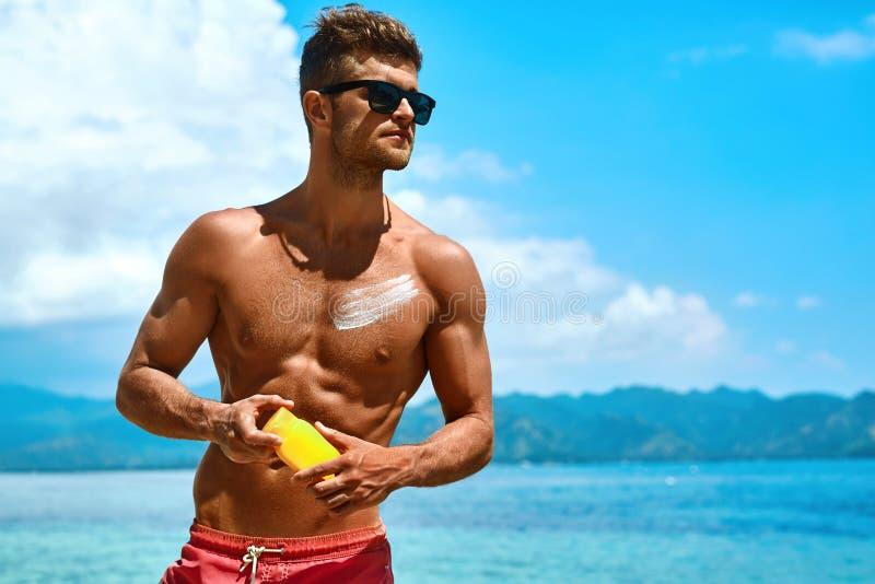 Άτομο που μαυρίζει χρησιμοποιώντας την κρέμα σώματος φραγμών ήλιων στη θερινή παραλία στοκ εικόνες