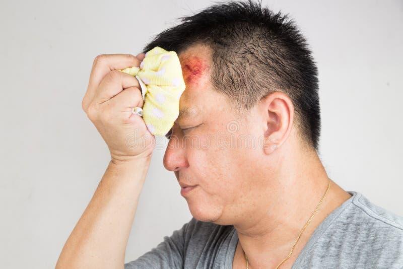 Άτομο που μεταχειρίζεται την τραυματισμένη επίπονη πρησμένη πρόσκρουση μετώπων του με το icep στοκ φωτογραφία με δικαίωμα ελεύθερης χρήσης