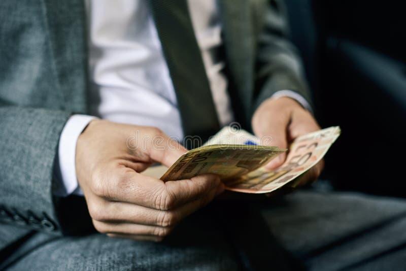 Άτομο που μετρά τους ευρο- λογαριασμούς στο πίσω μέρος ενός αυτοκινήτου στοκ εικόνες με δικαίωμα ελεύθερης χρήσης