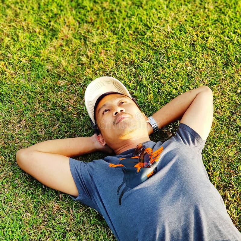 Άτομο που ξαπλώνει στη χλόη στοκ φωτογραφία