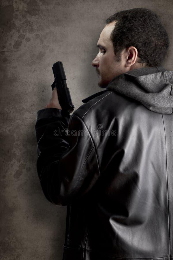 Άτομο που οπλίζεται με το πυροβόλο όπλο στη μαύρη κατασκευασμένη ανασκόπηση στοκ εικόνες
