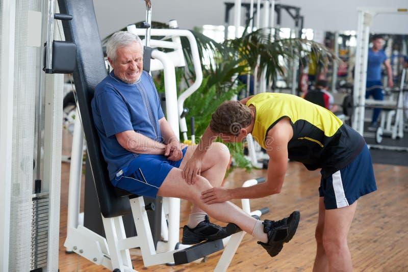 Άτομο που πάσχει από τον πόνο γονάτων στη γυμναστική στοκ φωτογραφία