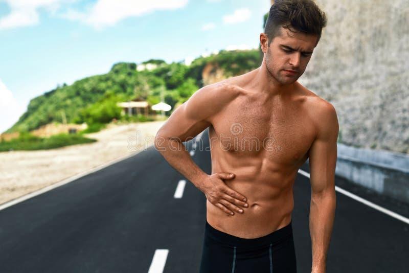 Άτομο που πάσχει από τον πόνο στομαχιών μετά από να τρέξει υπαίθρια Αθλητικός τραυματισμός στοκ φωτογραφία