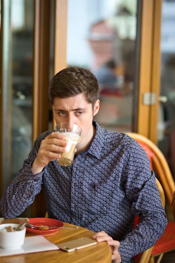 Άτομο που πίνει το μεγάλο latte σε έναν πίνακα καφέδων στοκ εικόνες με δικαίωμα ελεύθερης χρήσης