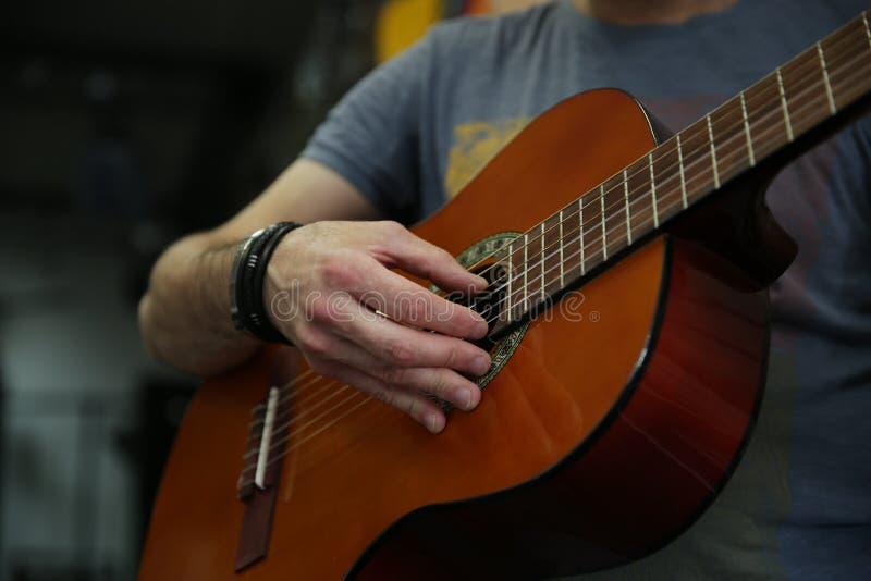 Άτομο που παίζει μια κλασική κιθάρα Μαζεύει με το χέρι επάνω τις σειρές στην κιθάρα στοκ φωτογραφία