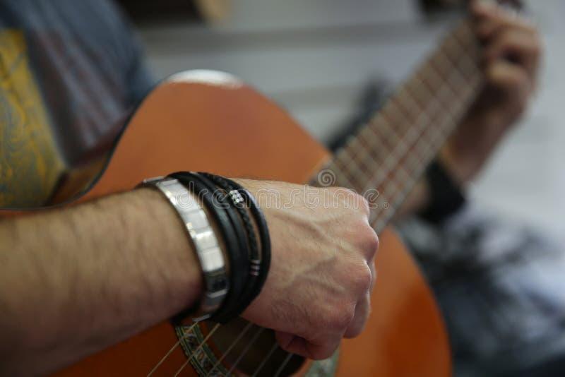 Άτομο που παίζει μια κλασική κιθάρα Μαζεύει με το χέρι επάνω τις σειρές στην κιθάρα στοκ εικόνα