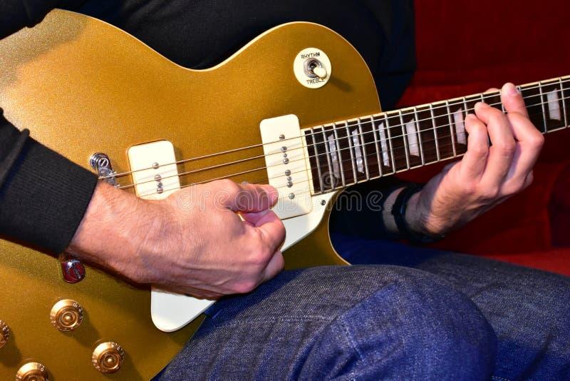 Άτομο που παίζει μια χρυσή τοπ ηλεκτρική κιθάρα P90 επαναλείψεις, λεπτομέρειες σωμάτων και λαιμών: Εξογκώματα, rosewood fretboard στοκ εικόνες