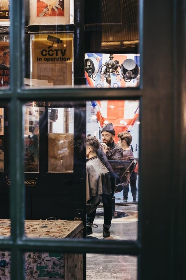 Άτομο που παίρνει ένα κούρεμα μέσα στους κουρείς Hobbs, κατάστημα κουρέων που βρίσκεται μέσα στην αγορά δήμων, Λονδίνο, UK στοκ φωτογραφίες