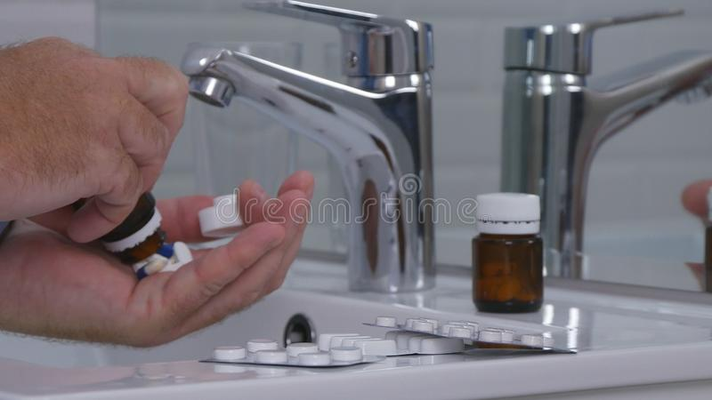 Άτομο που παίρνει ένα μίγμα των φαρμάκων και των χαπιών στο λουτρό στοκ φωτογραφίες με δικαίωμα ελεύθερης χρήσης