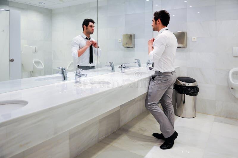 Άτομο που παίρνει ντυμένο σε έναν δημόσιο χώρο ανάπαυσης με τον καθρέφτη στοκ εικόνα