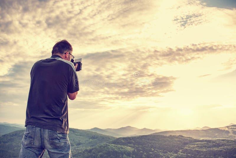 Άτομο που παίρνει την εικόνα τοπίων στον τουρίστα υδρονέφωσης με τη κάμερα και το τρίποδο στοκ φωτογραφία