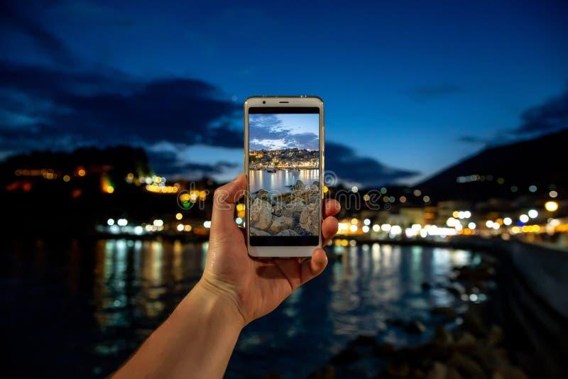 Άτομο που παίρνει τη φωτογραφία στο κινητό τηλεφωνικό smartphone στην πόλη θάλασσας βραδιού στοκ εικόνες