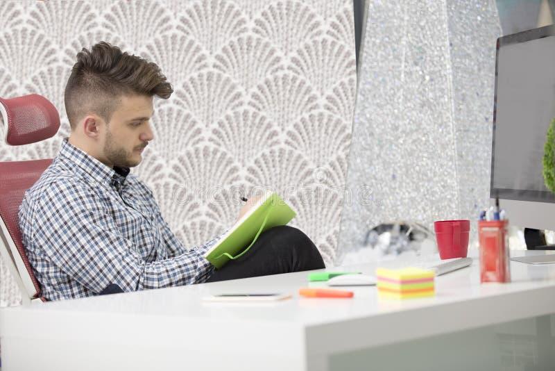 Άτομο που παίρνει τις σημειώσεις κάτω από το νέο φορητό προσωπικό υπολογιστή του στην εργασία στο γραφείο πρωινού με τον καφέ στοκ φωτογραφία με δικαίωμα ελεύθερης χρήσης