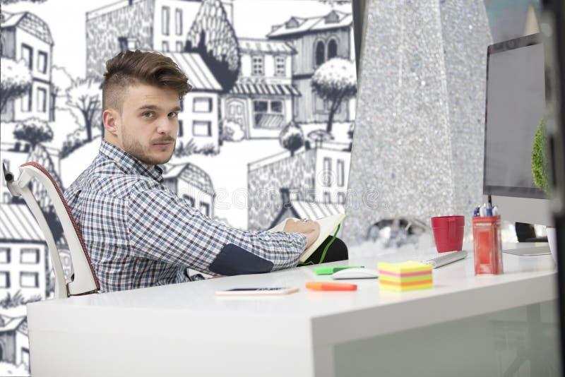 Άτομο που παίρνει τις σημειώσεις κάτω από το νέο φορητό προσωπικό υπολογιστή του στην εργασία στο γραφείο πρωινού με τον καφέ στοκ φωτογραφία