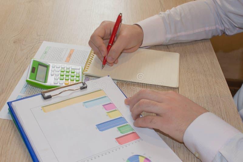 Άτομο που παίρνει τις σημειώσεις, υπολογιστής για τον πίνακα Κίνητρο επιτυχίας, οικονομικές ροές, πλούτος στοκ φωτογραφία με δικαίωμα ελεύθερης χρήσης