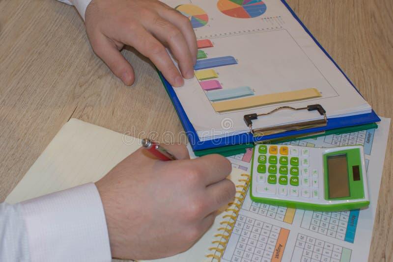 Άτομο που παίρνει τις σημειώσεις, υπολογιστής για τον πίνακα Κίνητρο επιτυχίας, οικονομικές ροές, πλούτος στοκ φωτογραφίες με δικαίωμα ελεύθερης χρήσης