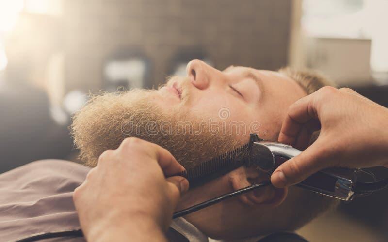 Άτομο που παίρνει το κούρεμα από το hairstylist στο barbershop στοκ φωτογραφία