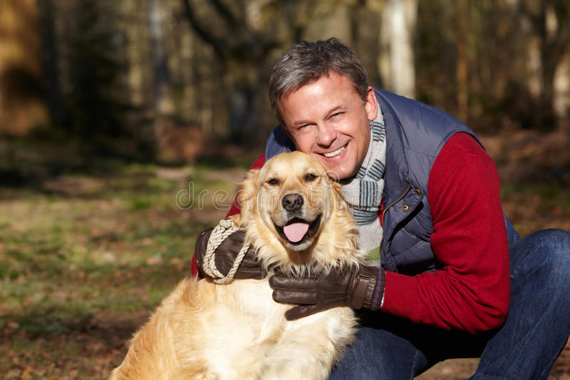 Άτομο που παίρνει το σκυλί στον περίπατο μέσω των ξύλων φθινοπώρου στοκ εικόνες με δικαίωμα ελεύθερης χρήσης