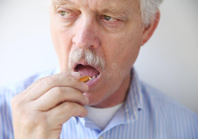 Άτομο που παίρνει το χάπι πετρελαίου ψαριών στοκ φωτογραφία