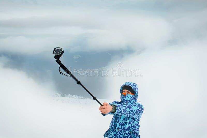 Άτομο που παίρνει selfie στο βουνό που χρησιμοποιεί τη κάμερα δράσης στοκ εικόνα με δικαίωμα ελεύθερης χρήσης