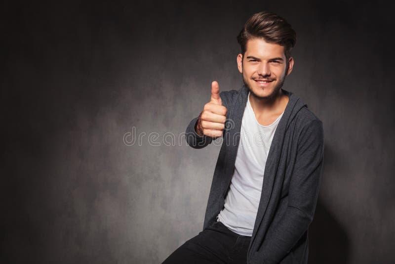 Download Άτομο που παρουσιάζει θετική χειρονομία χεριών καθμένος στο στούντιο Στοκ Εικόνα - εικόνα από μαύρα, θετικός: 62721667