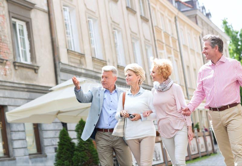 Άτομο που παρουσιάζει κάτι στους φίλους περπατώντας στην πόλη στοκ εικόνες