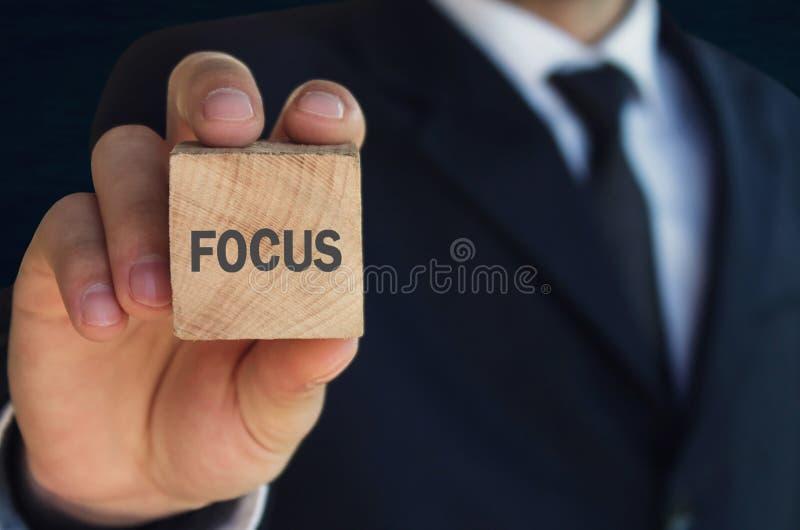 Άτομο που παρουσιάζει ξύλινο κύβο με μια γραπτή λέξη εστίασης στοκ φωτογραφίες