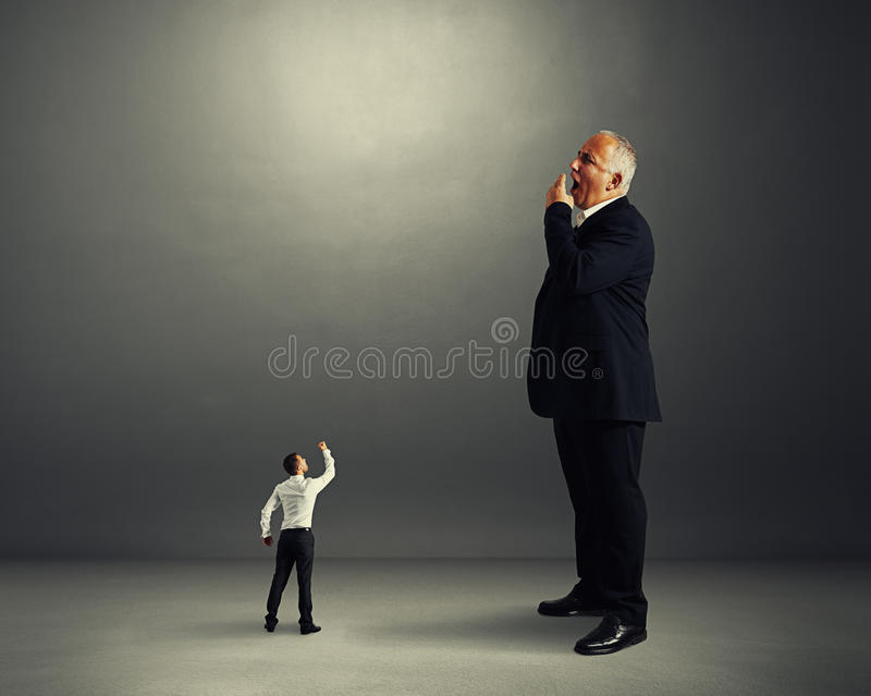 Άτομο που παρουσιάζει πυγμή στο μεγάλο χασμουμένος επιχειρηματία στοκ εικόνα με δικαίωμα ελεύθερης χρήσης