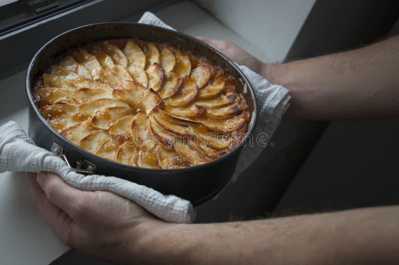 Άτομο που παρουσιάζει σπιτικό κέικ μήλων του με υπερήφανο στοκ φωτογραφίες