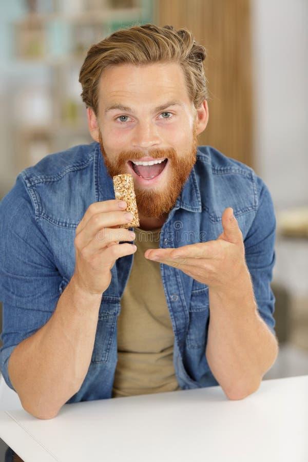 Άτομο που παρουσιάζει στο φραγμό δημητριακών τον που πηγαίνει να φάει στοκ φωτογραφίες