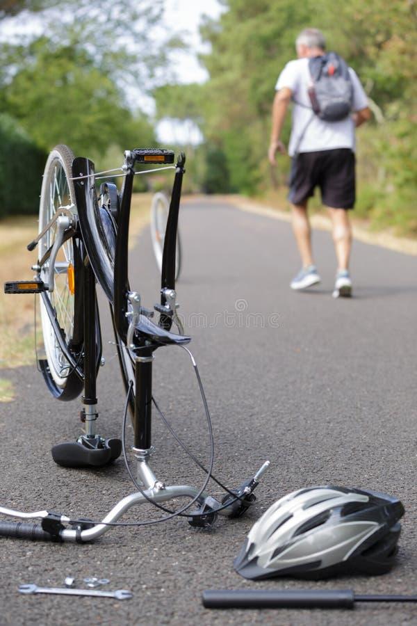 Άτομο που περπατά από την αναχώρηση του σπασμένου ποδηλάτου στοκ εικόνες