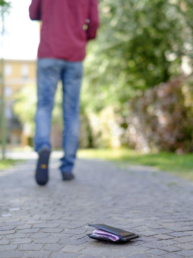 Άτομο που περπατά μετά από να χάσει το πορτοφόλι του στοκ φωτογραφία με δικαίωμα ελεύθερης χρήσης