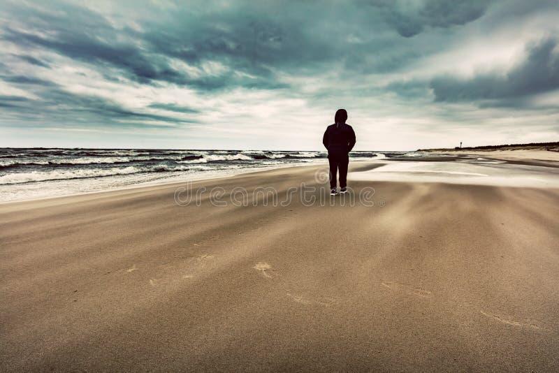 Άτομο που περπατά μόνο στην παραλία τη θυελλώδη θυελλώδη ημέρα στοκ εικόνα με δικαίωμα ελεύθερης χρήσης