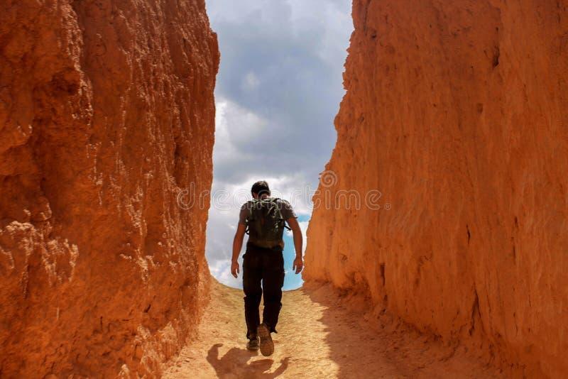 Άτομο που περπατά προς τον ουρανό σε μια στενωπό του κόκκινου/πορτοκαλιού βράχου στοκ φωτογραφίες