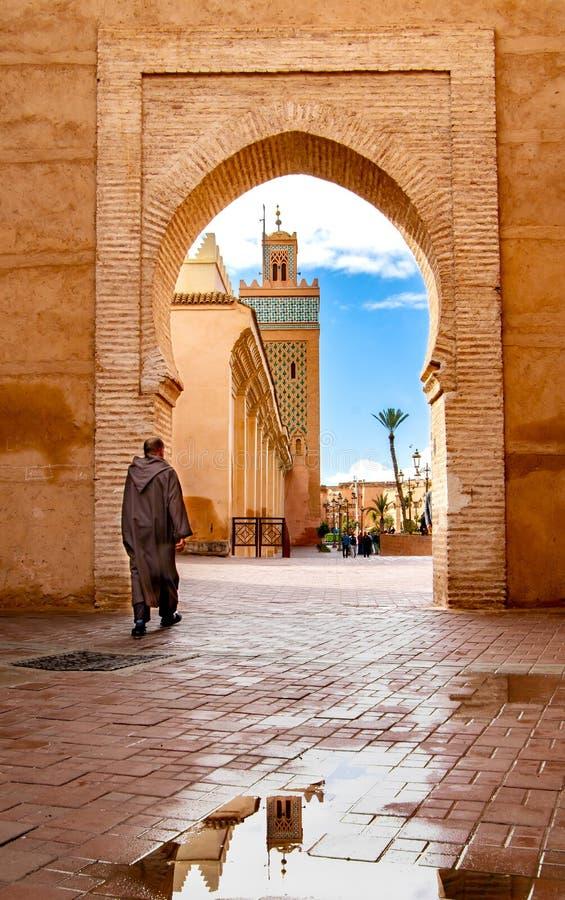 Άτομο που περπατά προς το μουσουλμανικό τέμενος στο Μαρακές στοκ εικόνα με δικαίωμα ελεύθερης χρήσης