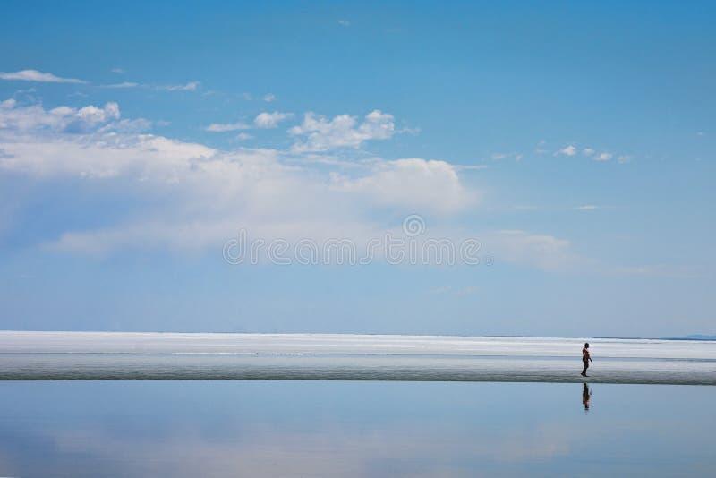 Άτομο που περπατά στην ακτή της λίμνης στοκ εικόνα