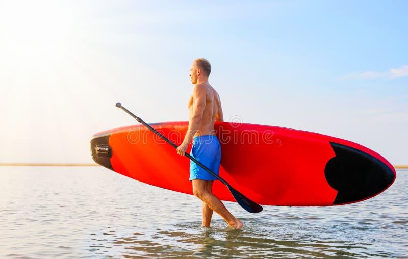 Άτομο που περπατά στο νερό με τον πίνακα ΓΟΥΛΙΑΣ στοκ εικόνες