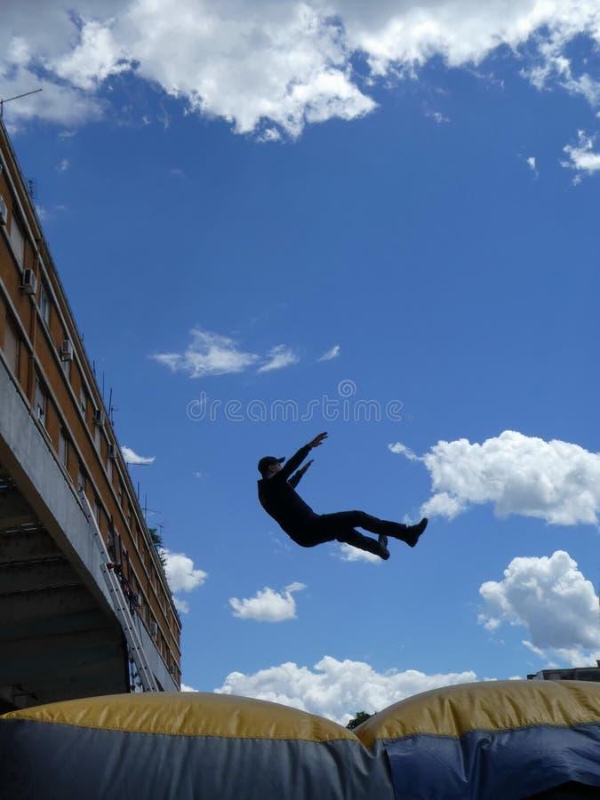 Άτομο που πηδά κάτω στο διογκώσιμο μαξιλάρι διάσωσης γνωστό επίσης ως μαξιλάρι άλματος ή προσκέφαλο αέρα στοκ εικόνες