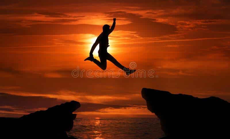 Άτομο που πηδά πέρα από το βάραθρο μεταξύ δύο δύσκολων βουνών στοκ εικόνες