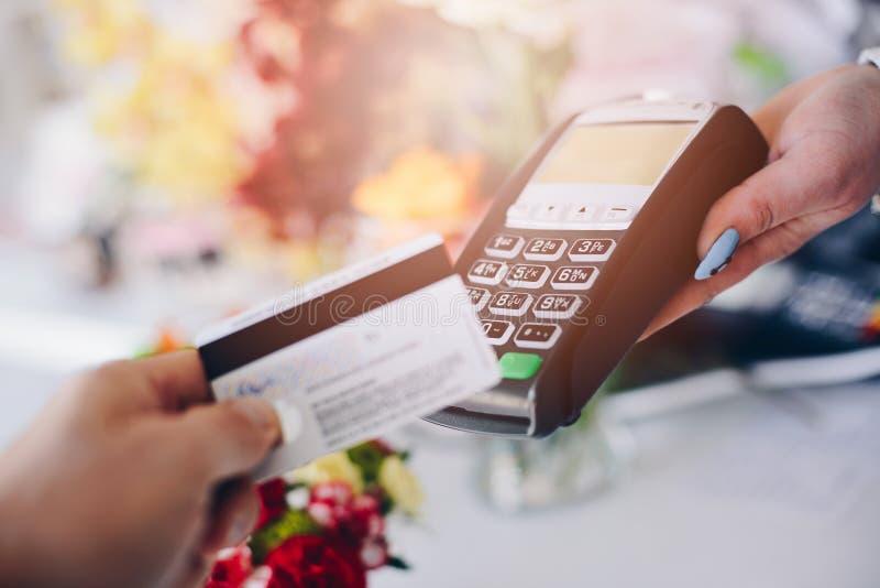 Άτομο που πληρώνει για τα λουλούδια με τη χρεωστική κάρτα του στοκ εικόνα