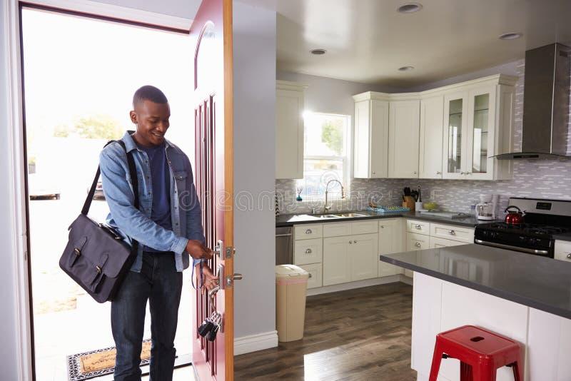 Άτομο που προέρχεται κατ' οίκον από την εργασία και την ανοίγοντας πόρτα του διαμερίσματος στοκ φωτογραφία