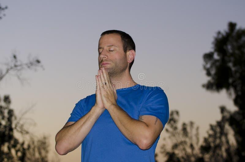Άτομο που προσεύχεται μόνο στο σούρουπο σε ένα υπαίθριο πάρκο στοκ εικόνες