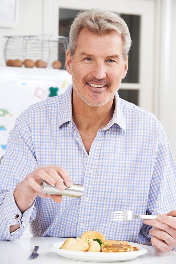 Άτομο που προσθέτει στο σπίτι το άλας στο γεύμα στοκ φωτογραφία με δικαίωμα ελεύθερης χρήσης