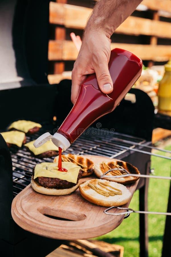 Άτομο που προσθέτει το κέτσαπ στα burgers που μαγειρεύεται υπαίθρια στη σχάρα στοκ εικόνες